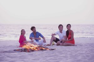 Four people on the beach with a fire burning